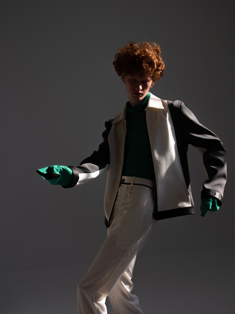 Man with red hair wearing a black and white suit dancing in a sun ray