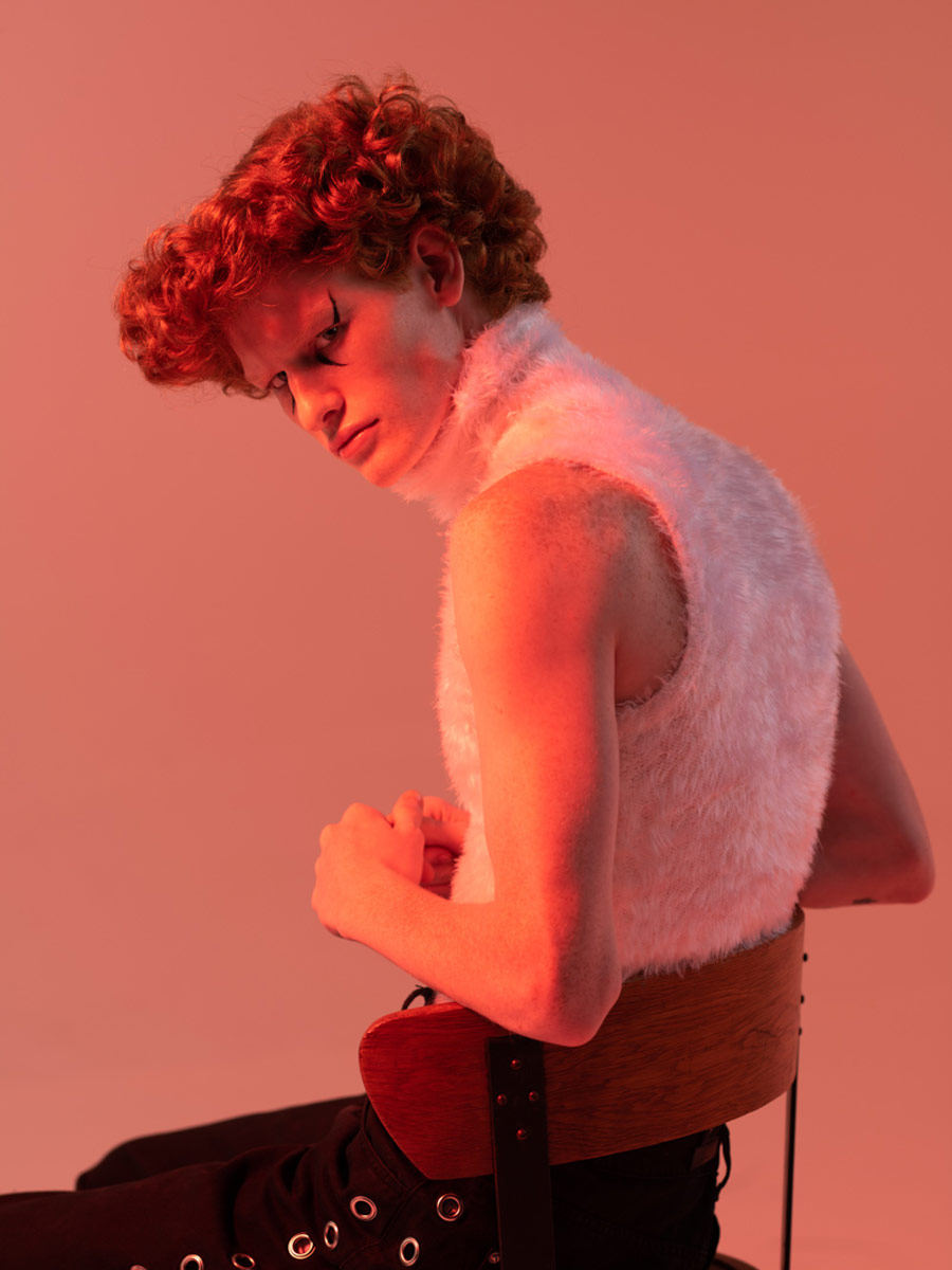 Portrait of a man with red hair and red light sitting on a chair looking over his shoulder