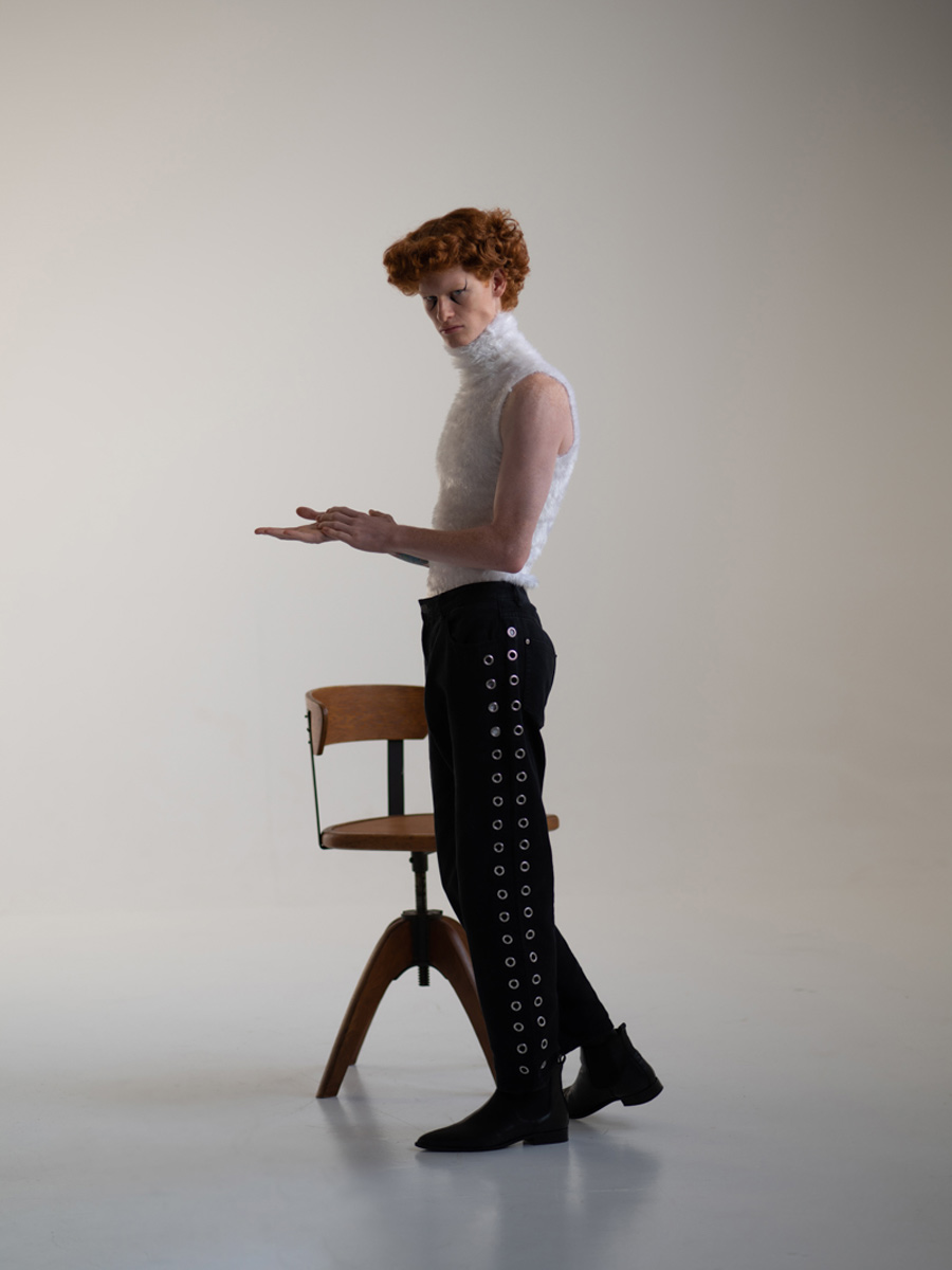 Man with red hair standing beside a chair
