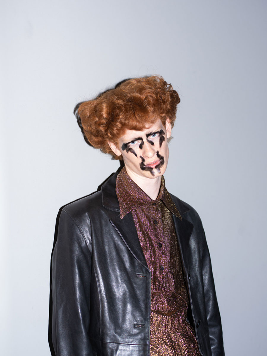 Man withe red hair and black make up wearing a leather jacket
