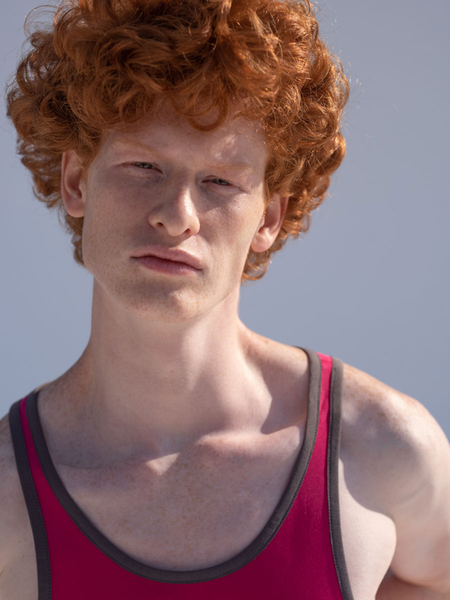 Boy with red hair wearing pink play suit