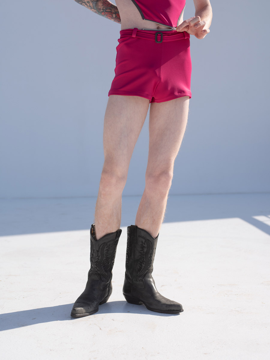 Legs of a boy with red hair wearing pink play suit