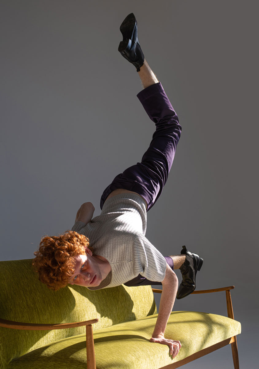 Man with red hair and bronze make up standing on a green couch with his legs on the air