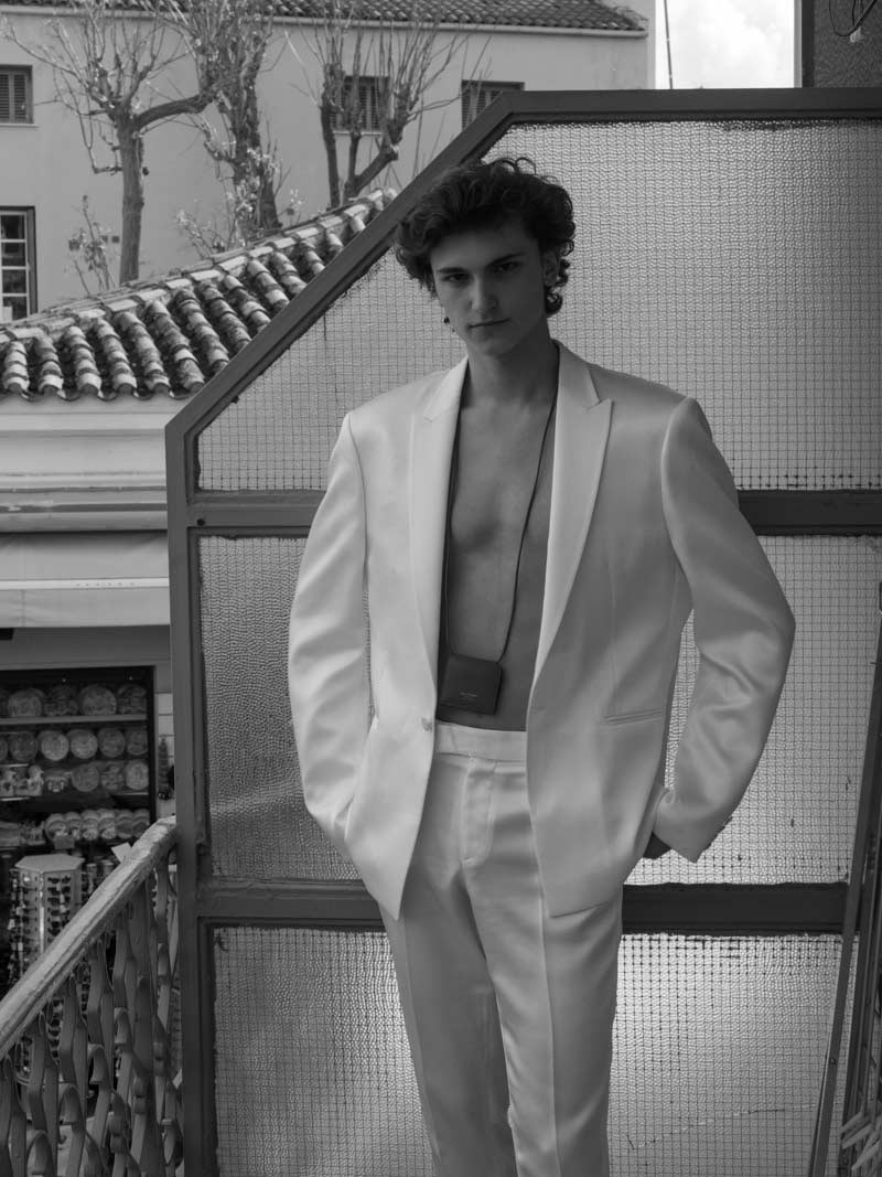 Man wearing white suit at a balcony black and white