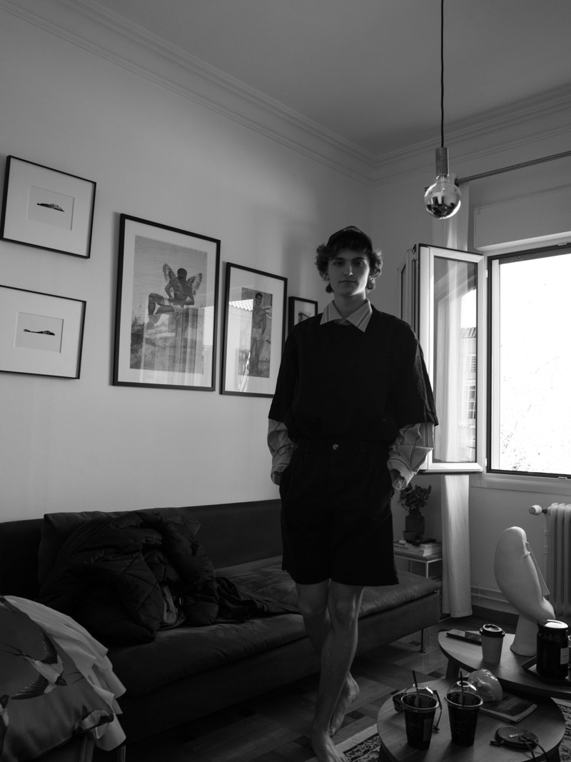 Man with hat standing in a room full of paintings on black and white