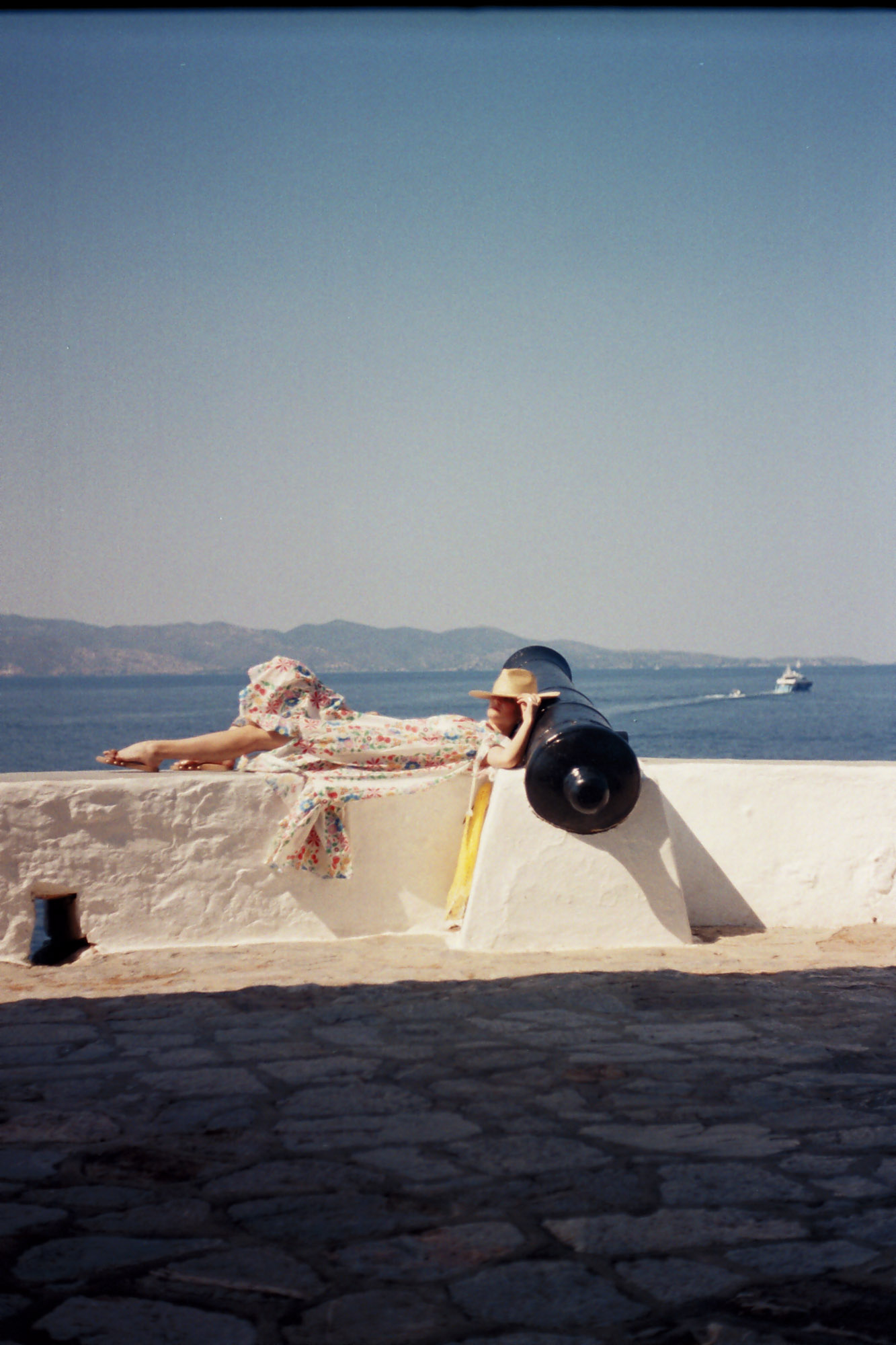 A woman laying down to a canon on a summer dress and a straw hat