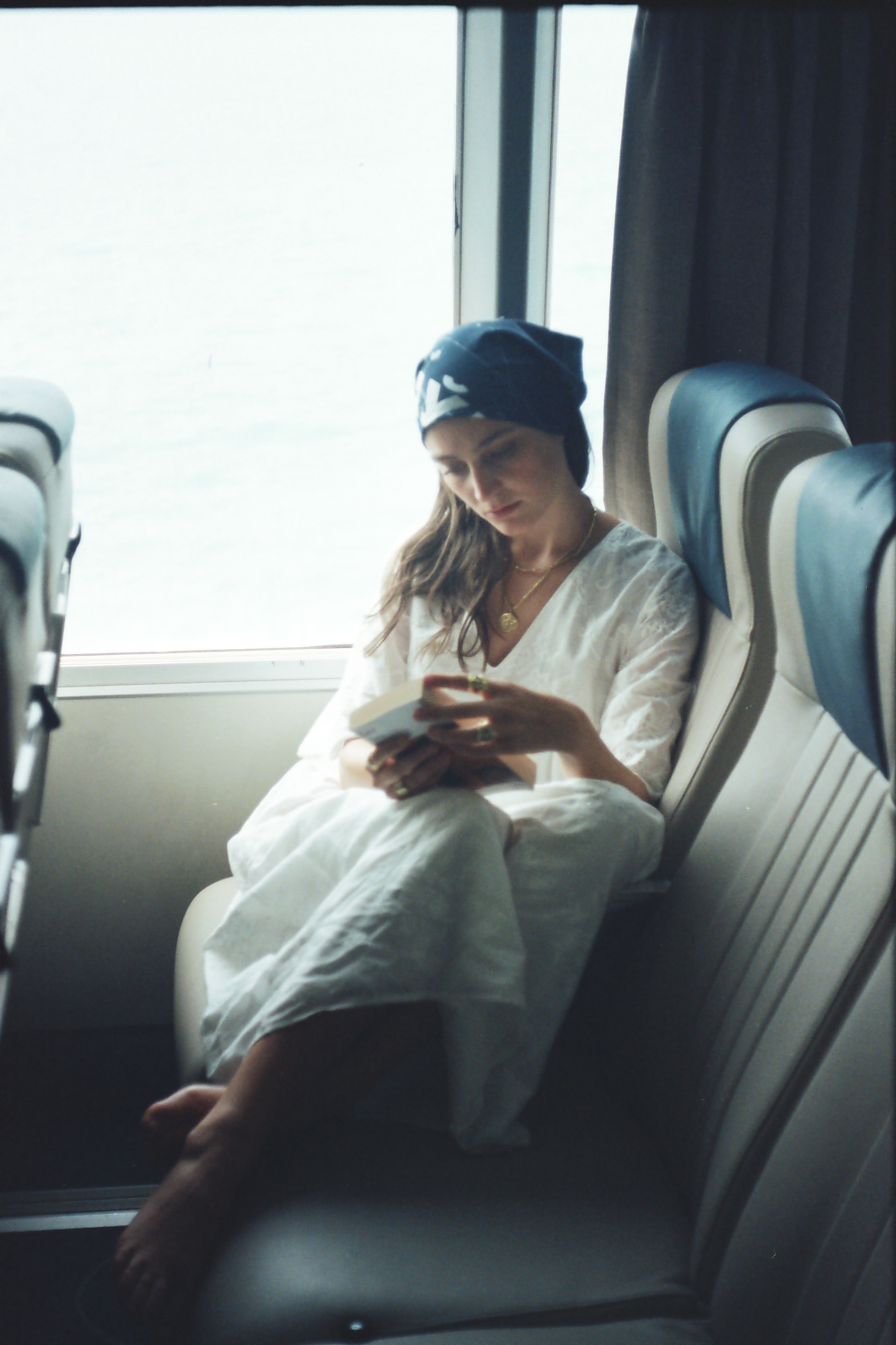A woman wearing a white dress reading a book on a ferry boat seat