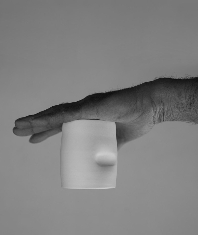 A hand holding a white cup upside down