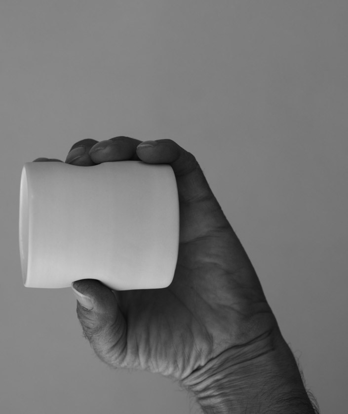 A hand holding a white cup